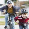 Father (20s) and son (4 years) riding bicycles.  Focus on boy.